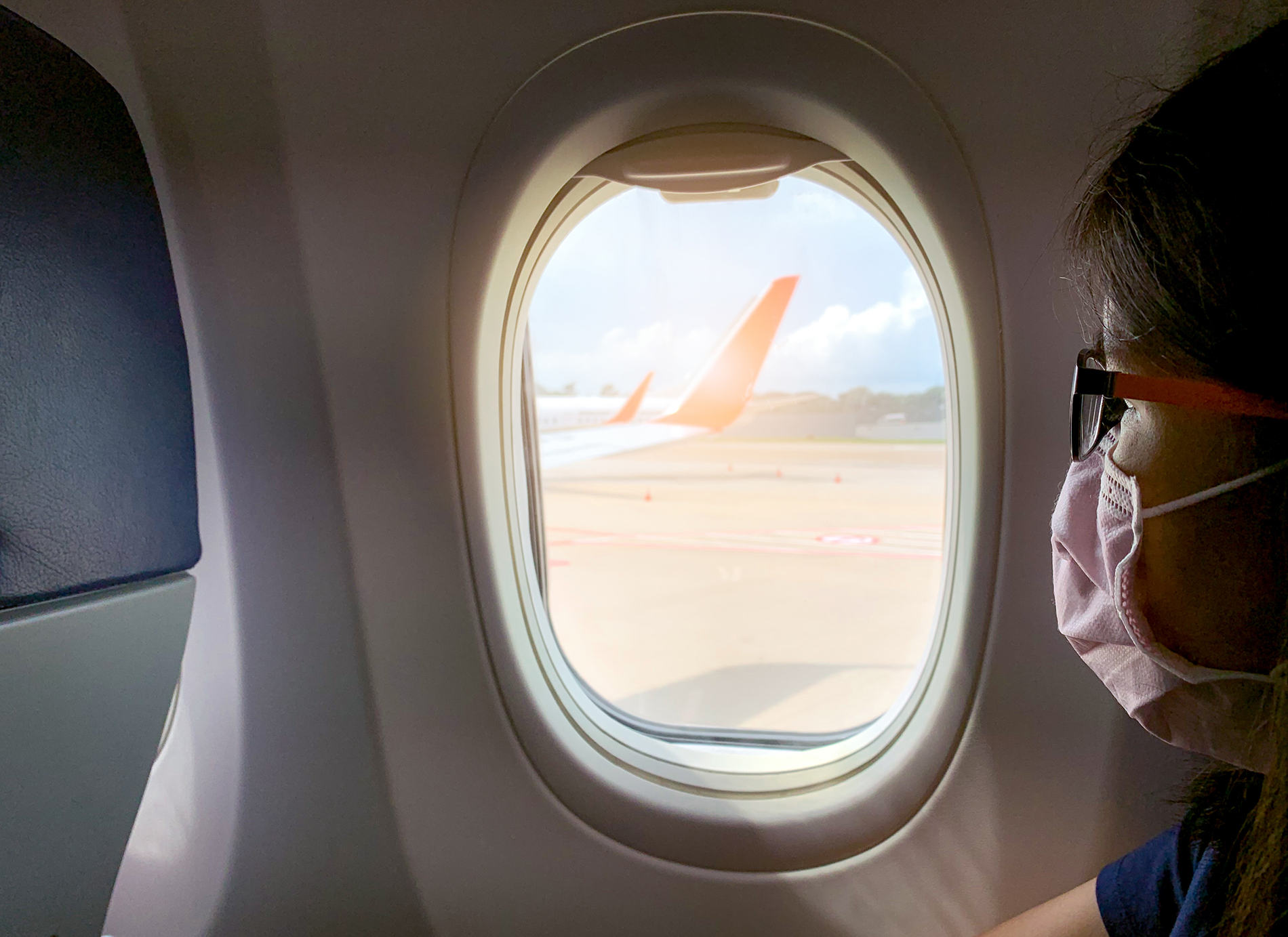 Woman with Face Mask in Airplane