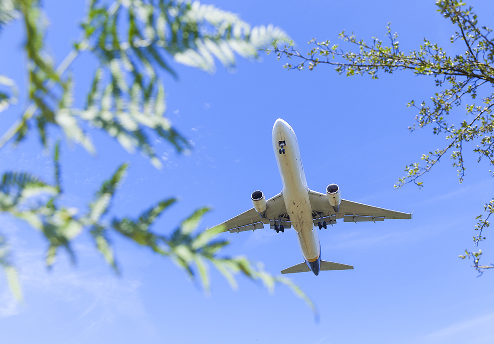 Plane in blue Sky - A greener way to travel